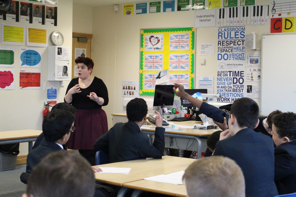 A white woman with red hair is talking with a classroom of secondary school students who have their hands in the air.
