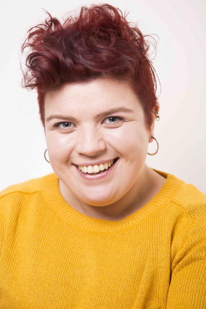 A headshot of Sarah Emmott. She is white and has curly red hair and a yellow jumper. She's smiling.