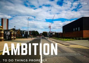 Photograph of a road in Ordsall, Salford leading towards the city of Manchester. In the distance are high rise buildings and cranes. The sky is blue, but cloudy. Over the photograph the word Ambition is typed in large capital letters, below it the words 'To do things properly'.