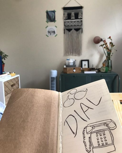 Photograph of worn brown notebook, open on the first page with remnants of several torn our pages on the spine of the book. On the plain paper is a drawing in biro. At the top left hand side of the page are three speech bubbles moving in sync with one another. In the centre of the page on an diagonal upwards angle; the word Dial is written in capital letters. To the bottom write is a drawing of an old fashioned corded telephone. In the background of the photograph is bedroom furniture, photographs and a wall hanging.