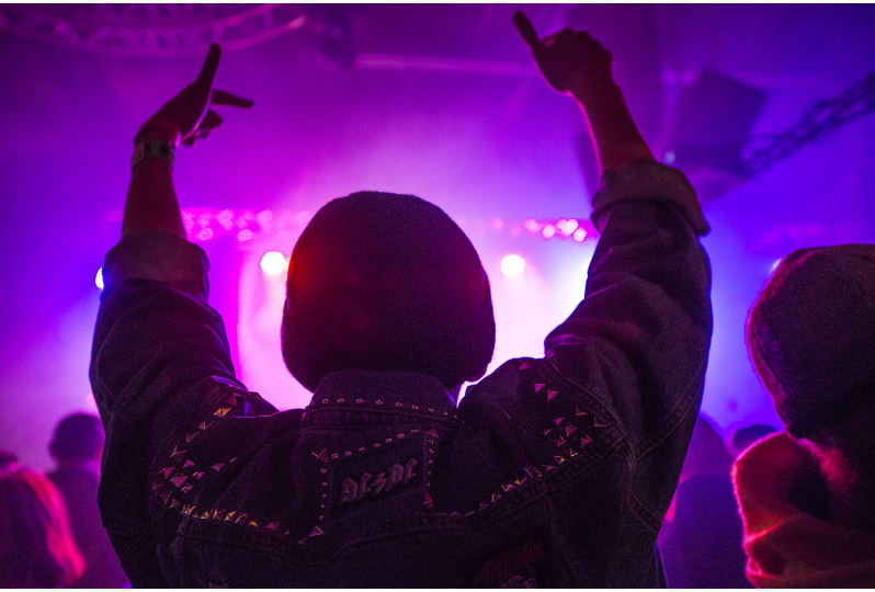 Photo taken from behind of a person wearing a denim studded jacket with an AC/DC patch on the collar. They are holding their arms aloft in joy as they dance on a dance floor which is bathed in neon pink and purple light.