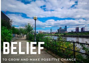 Photograph of a canal path in Ordsall, Salford leading towards the city of Manchester. In the distance are high rise buildings. The sky is blue, but cloudy. Over the photograph the word Belief is typed in large capital letters, below it the words 'To grow an make positive change'.