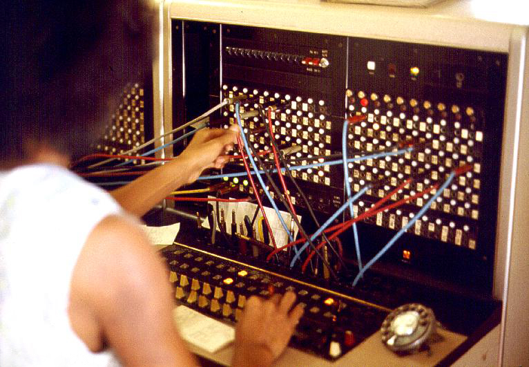 A photograph of a young black woman in a smart white sleeveless blouse operating an old-fashioned telephone operating system. The photograph is taken from behind the woman.